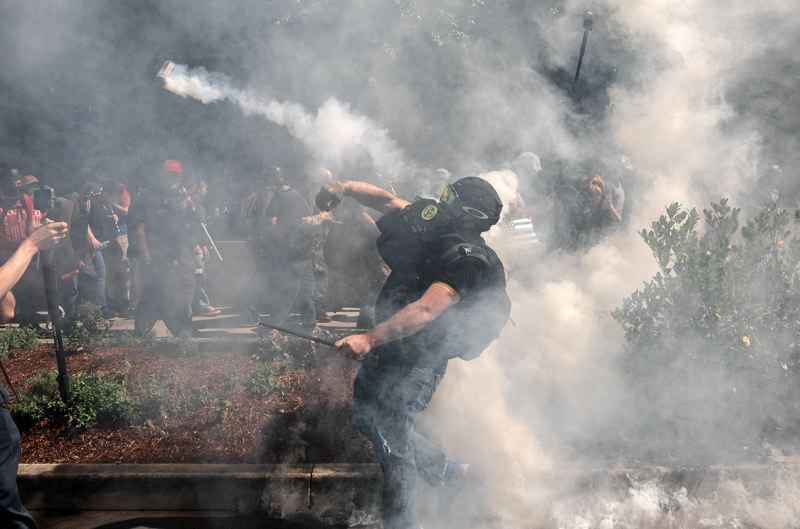 PMG PHOTO: JONATHAN HOUSE - A man hurls a smoke bomb during a street brawl in downtown Portland on Saturday, Aug. 22.