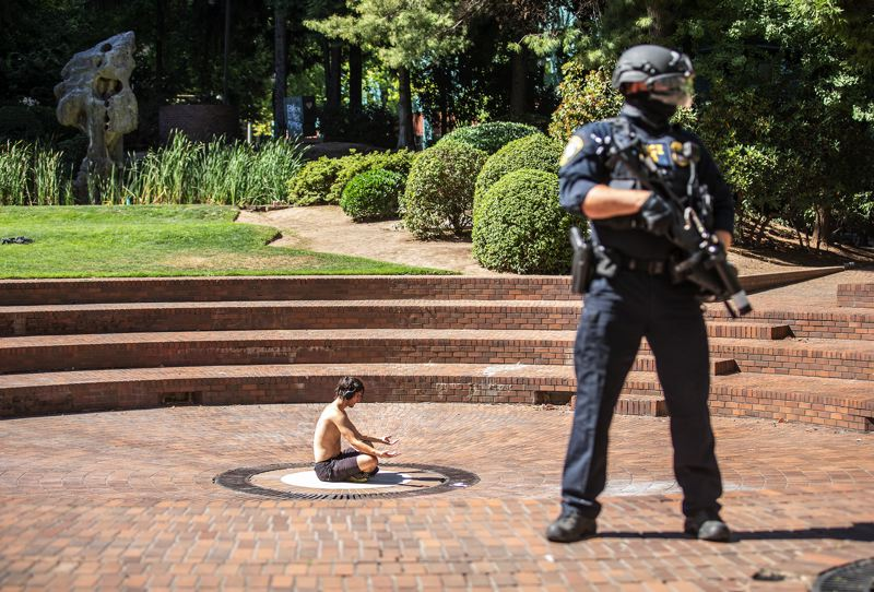 PMG PHOTO: JONATHAN HOUSE - A Department of Homeland Security officer stands guard outside Chapman Square after federal officers declared an unlawful assembly and pushed protesters out of the plaza. The shirtless man was pushed and shot at with crowd control munitions during the tumult.