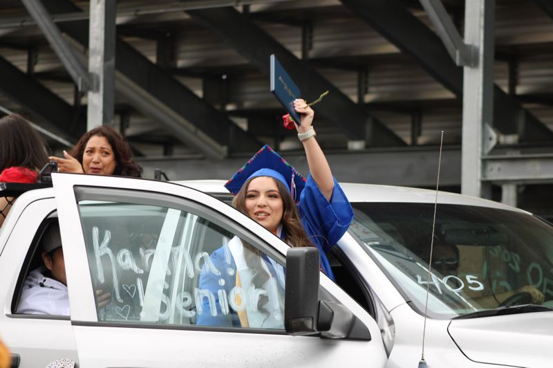 PMG FILE PHOTO: TERESA JACKSON  - Karina Hernandez waved her diploma to Madras High School staff who cheered for her as she left the drive-up graduation ceremony in June.