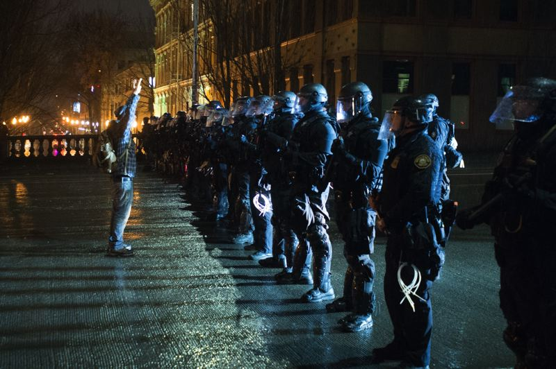 FILE - A lone protester shouts 'Hands up, don't shoot!' at Portland police in riot gear on the Burnside Bridge in 2017.
