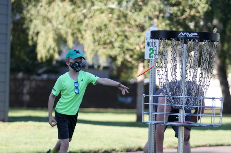 PMG PHOTO: PHILLIP HAWKINS - Eli Roper makes a short putt at the end of the first hole, which coincides with the beginning of the second hole, at Aurora's new disc golf course.