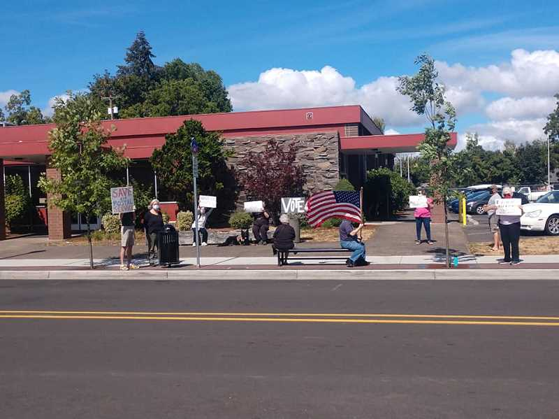 COURTESY PHOTO - A dozen protesters rallied outside the Woodburn Post Office on Aug. 22 to demonstrate against changes made to the postal service.