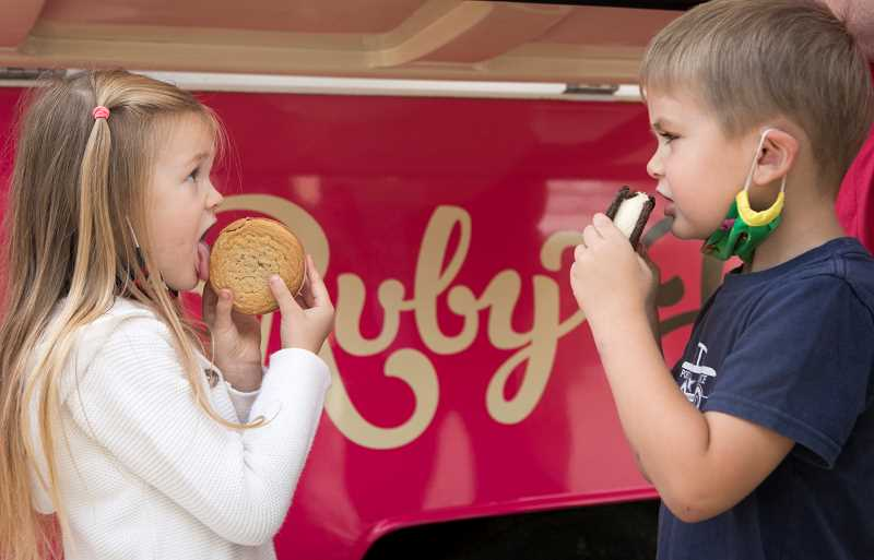 PMG PHOTO: JAIME VALDEZ - Cecilia Todd, 4, left, and Liam Wakefield, 5, enjoy an ice cream sandwich at the Ruby Jewell trailer at Bridgeport Village.