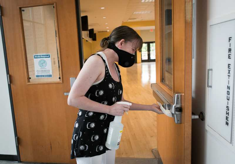 PMG PHOTOS: JAIME VALDEZ - Parker Gibson, a yoga instructor at Conestoga Recreation and Aquatic Center, wipes down a door handle to a door of the studio.
