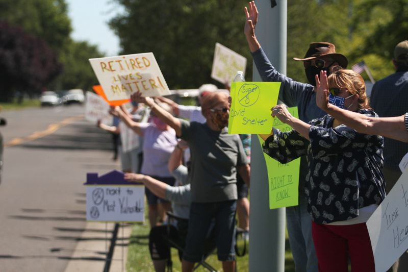 PMG PHOTO - Woodburn residents protest outside of the Super 8 Hotel in June after learning it would become the site of a COVID-19 isolation center in July. Demonstrators were critical of the location, next to several senior living care facilities, and being notified roughly two weeks before the contract would take effect.