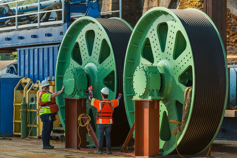 COURTESY: OREGON DEPARTMENT OF TRANSPORTATION  - Workers stand next to twelve foot diameter sheaves at the Interstate Bridge between Portland and Vancouver, Washington. The sheaves' axles, called trunnions, are being replaced next week. Both states have agreed to have another go at replacing the entire bridge, which is old, narrow, and inefficient.