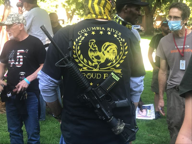 PMG PHOTO: ZANE SPARLING - A man strapped a long gun to his back while wearing a t-shirt for the Columbia River chapter of the Proud Boys organization during a memorial for Aaron Danielson, known as Jay, on Saturday, Sept. 5.