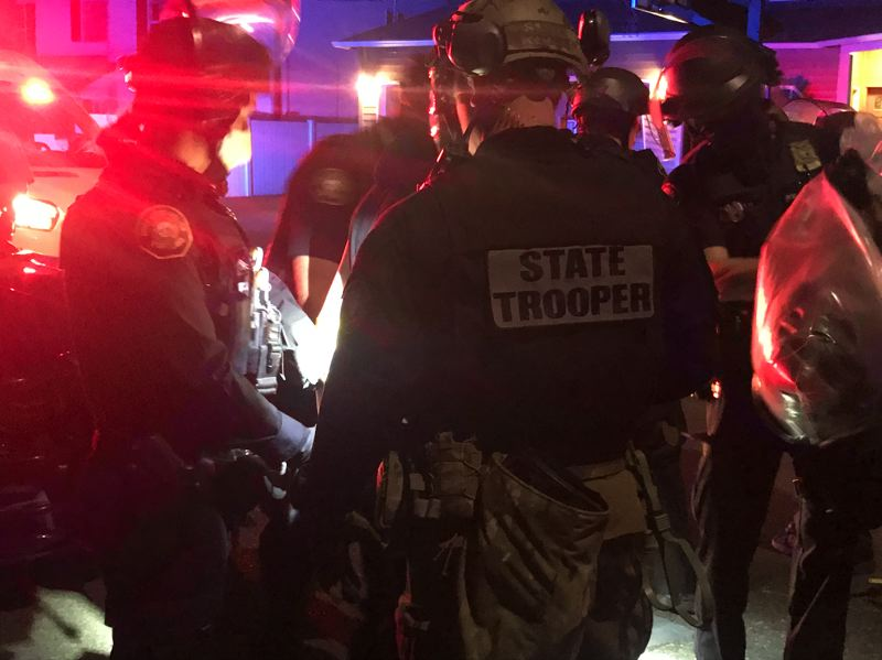 PMG PHOTO: ZANE SPARLING - Federally deputized Oregon State Police troopers processed arrestees on Southeast 117th Avenue during the 100th night of unrest in Portland on Saturday, Sept. 5.