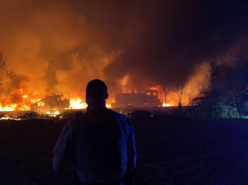 PHOTO COURTESY OF CLACKAMAS COUNTY SHERIFF'S OFFICE - A Clackamas County Sheriff's Deputy watches as a fire destroys much of the mill at RSG Forest Products in Molalla.