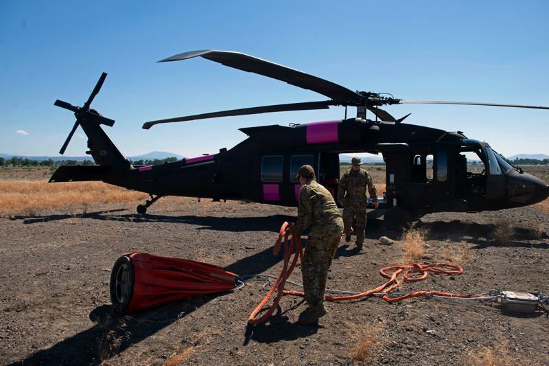 COURTESY PHOTO: OREGON NATIONAL GUARD - Oregon Army National Guard UH-60 Blackhawk pilot, Chief Warrant Officer 2 Michael Newgard and crew chief, Staff Sgt. Elana Cleveland out of Salem prepare the water bucket for aerial drops.