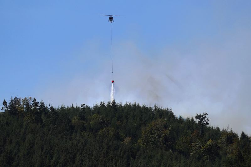 PMG PHOTO: JAIME VALDEZ - A helicopter dumps water on hotspots at the Powerline Fire near Henry Hagg Lake on Tuesday, Sept. 8.