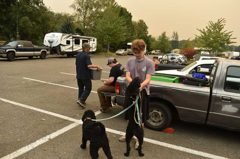 PMG PHOTO: RAYMOND RENDLEMAN - Estacada evacuee Jaydon Dow plays with his family's labradoddles Sissy and Missy in the parking lot of Clackamas Community College in Oregon City as his father Brent carries their tortoises past his brother Kory.