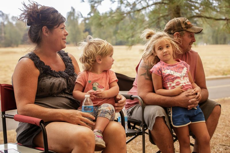 PMG PHOTO: JON HOUSE - Miranda House (left) and Blake House (right) hold their children Emma and Paisley as they wait for more news of their home in Colton threatened by the Unger Road Fire.