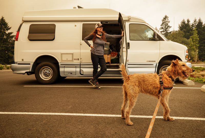 PMG PHOTO: JON HOUSE - Denise Everhart stands outside of her camper van in the parking lot of Clackamas Community College where her and dog Angus are taking refuge from the smoke that is choking out their home in Molalla.