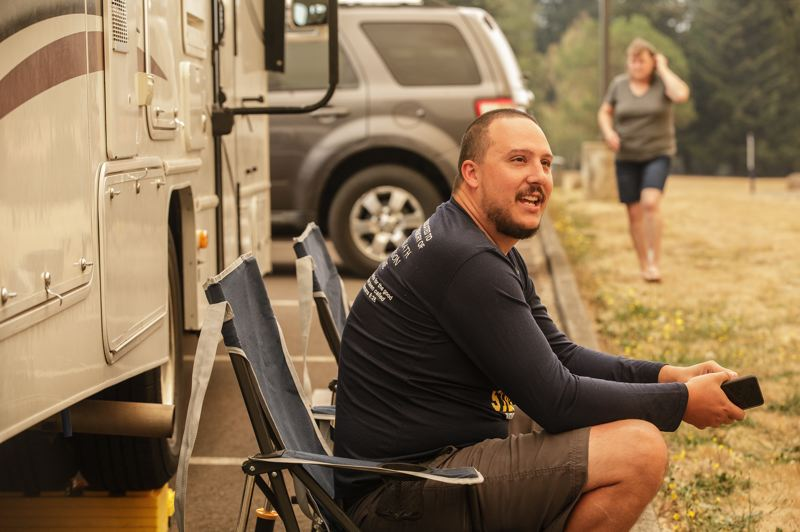 PMG PHOTO: JON HOUSE - Mike Meisch sits outside of his cousins motorhome at Clackamas Community College as they wait for updates on the fires that threaten his family's home in Molalla.