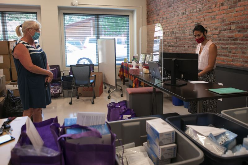 PMG PHOTO: JAIME VALDEZ - Ivette Heredia  of the Business Recovery Center in Forest Grove hands over supplies for fighting the coronavirus to Kerrie Andresen of Printek Industries.