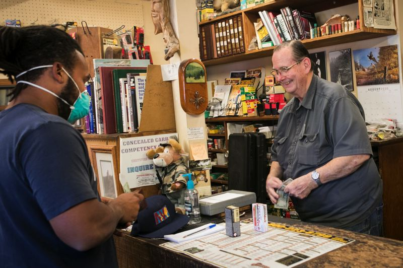PMG PHOTO: JAIME VALDEZ - Video production worker Deante Grinner (left) buys ammunition for his AR-15 rifle and Glock pistol from Kurt Mueller at H&K Gun Shop in Forest Grove. Grinner likes to support local businesses, Mueller likes to source ammo and limits it to one box per gun.