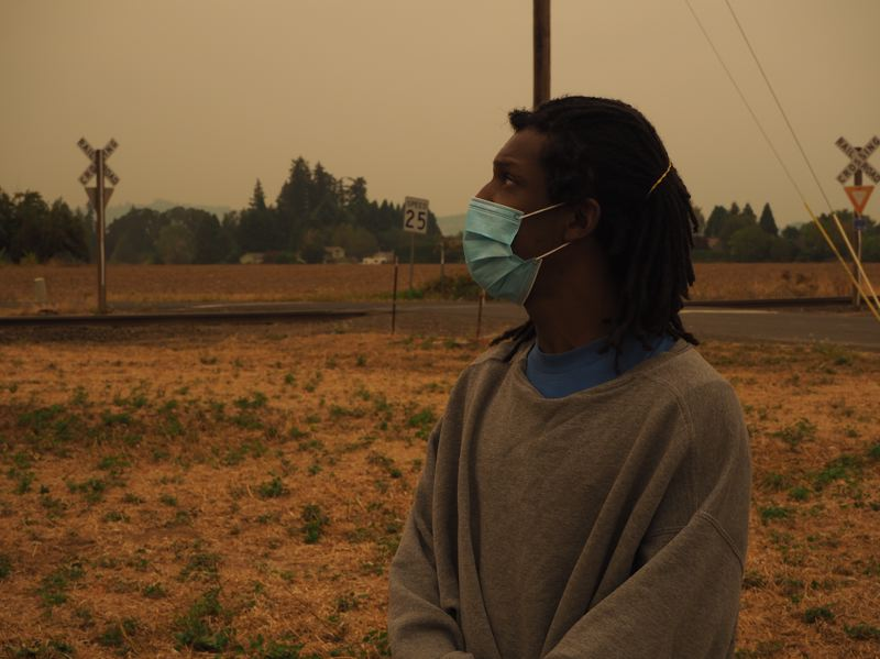 PMG PHOTO: MAX EGENER - Lorenzo Bennet looks up at a smoky sky at Open Door Counseling Center in Cornelius on Thursday, Sept. 10. Bennet is homeless and came to the outdoor day center for lunch.