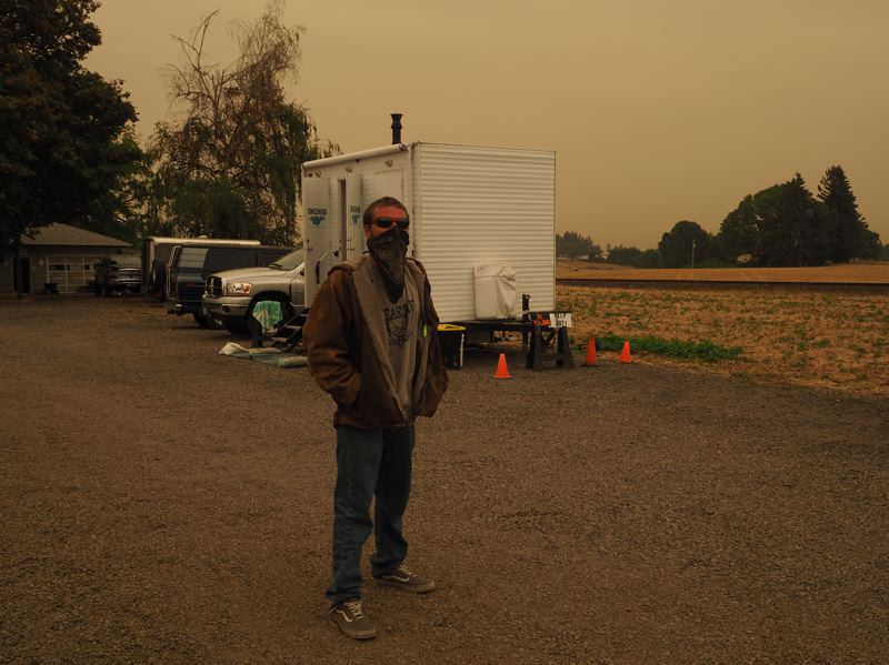 PMG PHOTO: MAX EGENER - Alan Moore, a homeless man who camps in western Washington County, stands in front of a mobile shower trailer at Open Door Counseling Center in Cornelius on Thursday, Sept. 10, amid smoky conditions.