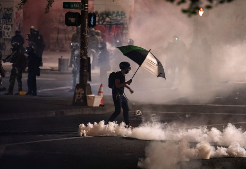 PMG FILE PHOTO - A protester wades through deployed tear gas during a downtown Portland demonstration in July.