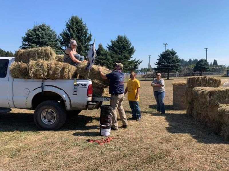 COURTESY OF ANNA WILLIAMSON - Volunteers unload bales of hay for livestock evacuated from wildfires.