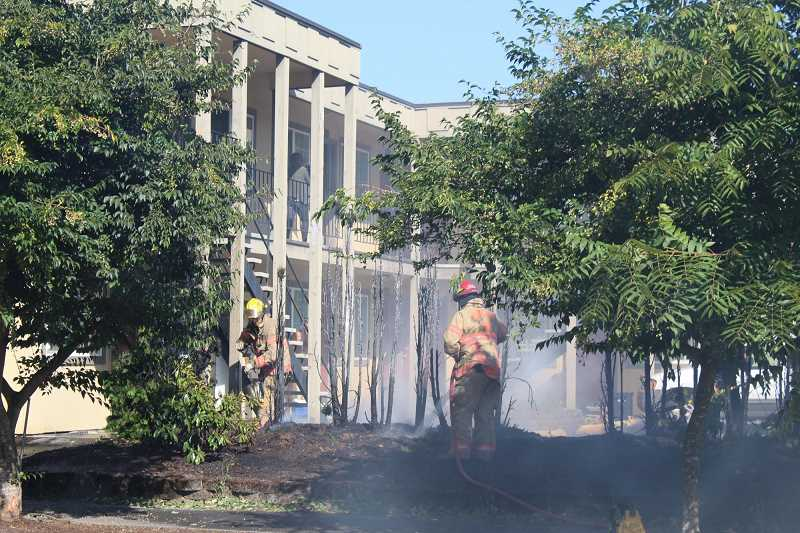 PMG PHOTO: COURTNEY VAUGHN - Fire crews attack a small brush fire outside a Southeast Portland apartment complex Tuesday, Sept. 8. Portland issued a fire emergency order Thursday, as heavy smoke and ash from nearby wildfires blanketed the city.