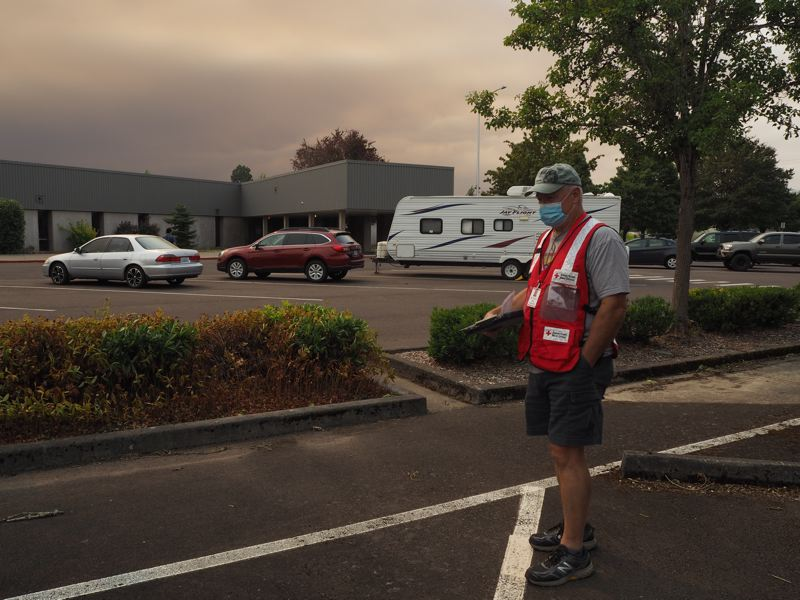 PMG PHOTO: MAX EGENER - American Red Cross volunteer Keith Mills stands at Neil Armstrong Middle School in Forest Grove, where evacuees from the Powerline Fire have used the parking lot as a shelter, with smoke in the sky behind him.