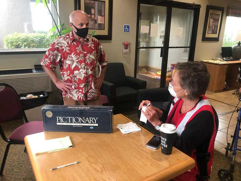 COURTESY OF ERIC SWENSON - Charlie Hintz, manager of Woodburn's Ray of Hope Thrift Store, and Red Cross coordinator Marilyn Agenbroad, discuss getting supplies to wildfire evacuees staying at Woodburn Super 8 Hotel Saturday. Hintz provided clothing vouchers and board games.