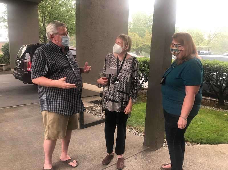 COURTESY OF ERIC SWENSON - Love INC Director Curt Jones, left, and Kathleen Gamble from Santiam Outreach Community Center, right, discuss options with an woman with special medical needs. The woman had been evacuated from Santiam Canyon due to the Beachie wildfire and is staying at Woodburn's Super 8 Hotel, which had been converted into a Red Cross center.