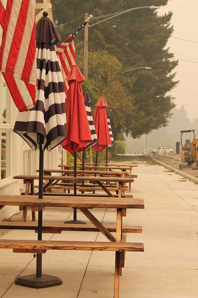PMG PHOTO: HOLLY BARTHOLOMEW - Typically, on Friday afternoons, tables outside the bars and restaurants of Willamette Falls Drive are busy with diners.  This Friday, they remained empty.