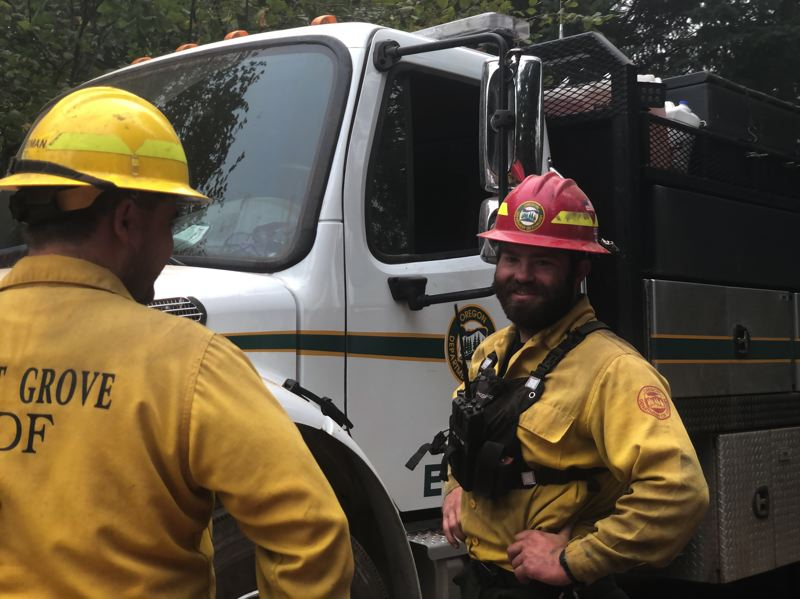 COURTESY PHOTO: FOREST GROVE FIRE & RESCUE - Firefighters converse near the scene of the Powerline Fire, which was declared to be contained and secured as of Sunday afternoon, Sept. 13.