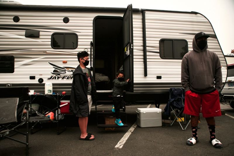 PMG PHOTO: JAIME VALDEZ - Keith Carroll and his family emerge from their travel trailer currently parked at the Clackamas Town Center mall Friday, Sept. 11 after they were forced to evacuate from their Oregon City home.