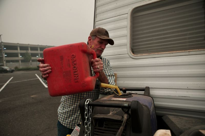 PMG PHOTO: JAIME VALDEZ - Dan Kubes of Colton refills the his generator with gas. Kubes and his wife evacuated their home Wednesday night and initially parked at Clackamas Community College before having to evacuate once again to Clackamas Town Center.