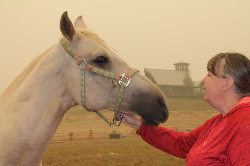 PMG PHOTO: HOLLY BARTHOLOMEW -  Barbara Knudsen, of Molalla speaks with one of her horses who was evacuated to Urbani's property in West Linn.