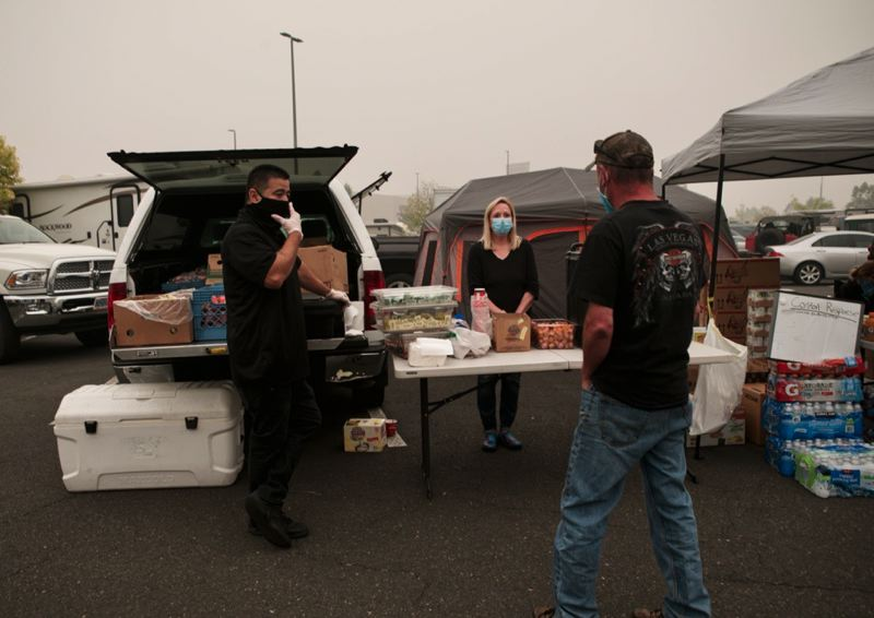 PMG PHOTO: JAIME VALDEZ - Union Gospel Church volunteers David Conrad (left) and Lori Quinney (center) distribute free food, coffee and medical supplies to evacuees of the wildfires in Clackamas County.