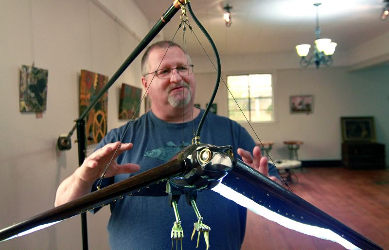 PMG PHOTO: MILES VANCE - Artist Carl Sumsion shows off his mechanical swing arm raven lamp that's on display — and for sale — at the newly-opened Steampunk Furniture in Rainier.