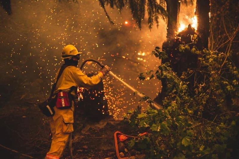 COURTESY PHOTO: CLACKAMAS FIRE - A firefighter works to put out flames caused by the Riverside fire.