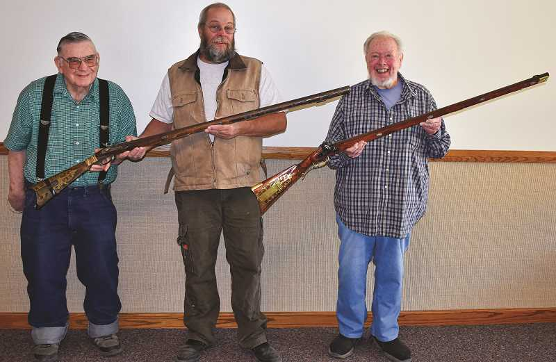 RAMONA MCCALLISTER - Members of the Beaver State Historical Gunmaker's Guild display the original Kentucky Muzzle Loader that Doug Ashcraft passed to his grandson, Justin Radabaugh, and the replica, recently presented to the Ashcraft family. From Left: Ernie McKenzie, Tom Cooper (holding the original muzzle loader), and Jim Malloy (holding the replica).