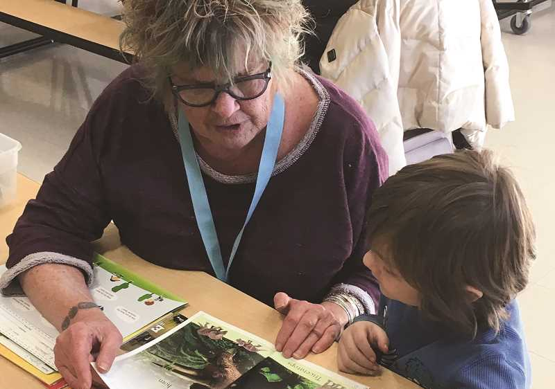PHOTO CONTRIBUTED BY SMART READING PROGRAM - A volunteer reads to an elementary student at Crooed River Elementary during the 2019-2020 school year.