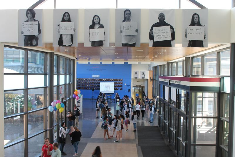 FILE - Clackamas High School's hallways featured posters of students and teachers holding printouts of phrases that have hurt them in 2016.
