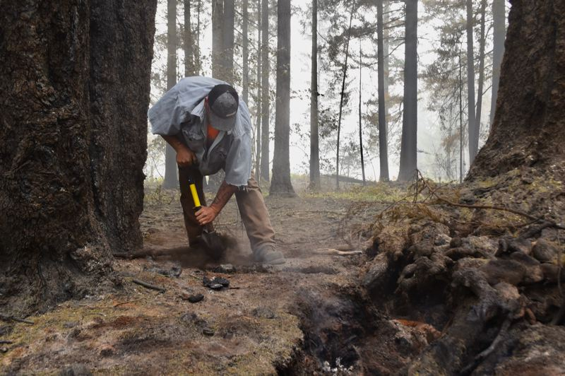 PMG PHOTO: BRITTANY ALLEN - Brian Rolen of Boring works to squelch a fire still burning in the roots of a tree at the site of Dodge Community Church in Estacada a week after the fire blazed through the neighborhood.