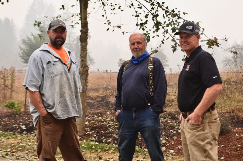 PMG PHOTO: BRITTANY ALLEN - Brian Rolen (left) and Donovan Bresko (right) have been helping Estacada residents like Doug (middle) fight spot fires on their properties since the Riverside Fire erupted two weeks ago.