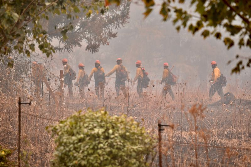 PMG PHOTO: BRITTANY ALLEN - A crew of firefighters from Knappa, Ore., sweep over the field where a house once stood on Hillockburn Road checking for hot spots.