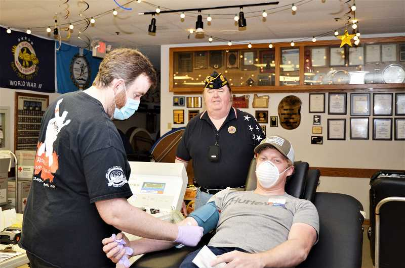 COURTESY PHOTO - At a Clackamas County Red Cross event in May, Brendon Stewart prepares to draw blood from John Parker with Mick Wilson in the background.