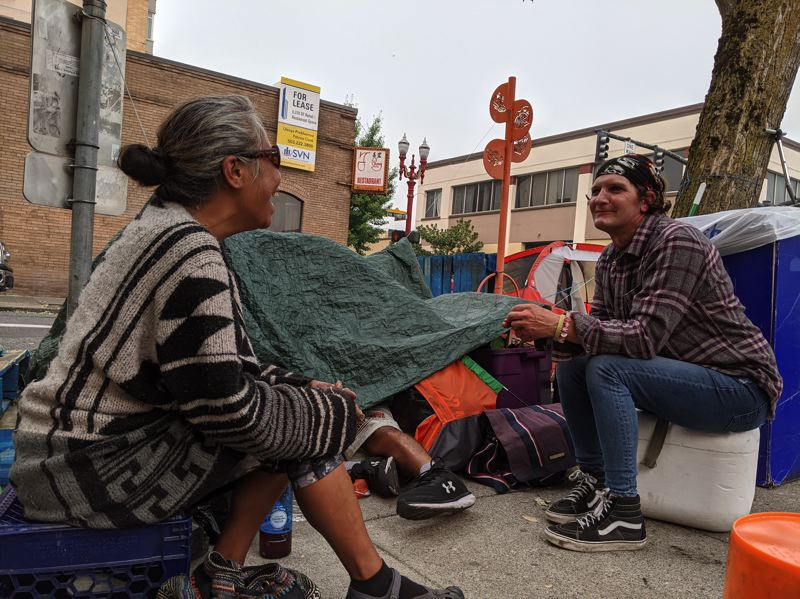 PMG: JOSEPH GALLIVAN  - At NW Davis St and 4th Ave, Kanani King, who goes by KK on the streets, talks to her friend Justine Warby, who lives in a shelter. King says the smoke doesn't bother her, it's just a smell.