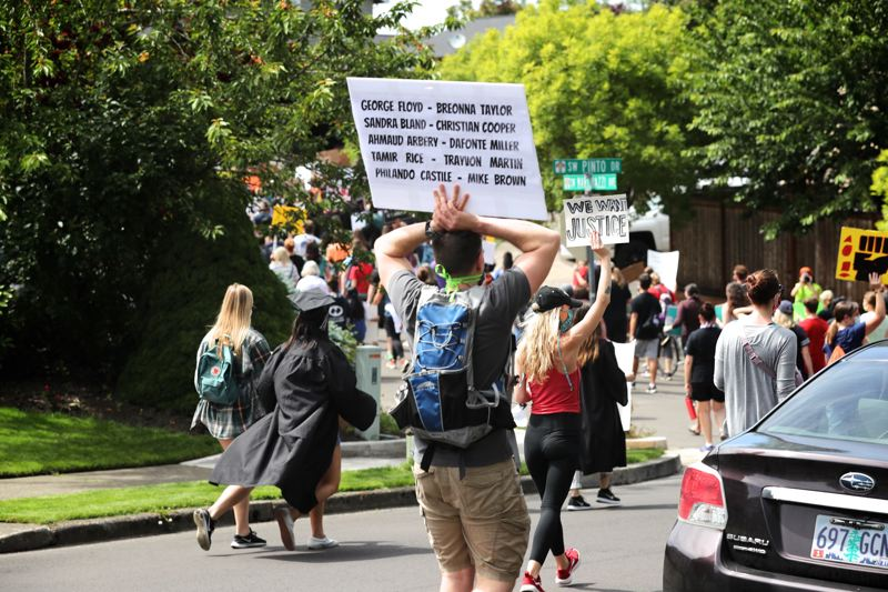 PMG PHOTO: JAIME VALDEZ - A demonstrator marching from Tualatin to Tigard to protest police brutality in June holds a sign listing the names of several individuals who have died at the hands of police officers or in police custody across the United States.
