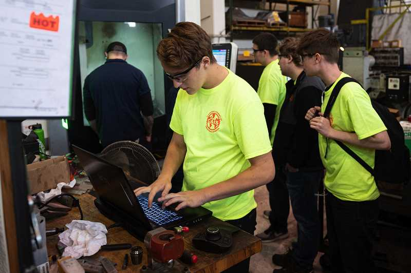 PMG PHOTO: CHRIS OERTELL - Clackamas Academy of Industrial Science student Eryck Stratton uses a computer to enter his name for a name tag that will be created on a CNC mill during a Manufacturing Day event at American Machine & Gear in Northwest Portland.