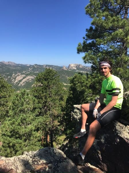 COURTESY PHOTO: PHILIP LADUCA - Philip LaDuca takes a break midway through his cross country bicycle trip from Oregon to Rhode Island in the Black Hills of South Dakota, with the back side of Mount Rushmore visible far behind his right shoulder.