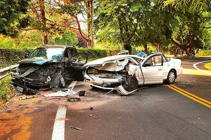 DAVID F. ASHTON - Witnesses say this grinding crash was the result of the driver of the white Toyota Avalon XL speeding on the curve, sideswiping a VW Jetta, and then losing control and smashing into this black Toyota head-on in the southbound lane.