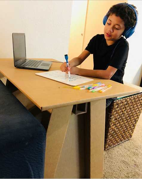 COURTESY PHOTO - A student working at cardboard desk. A parent teacher club hopes to raise $15,000 to give every student at McKay Elementary a cardboard desk.